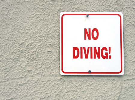 no diving sign: Red no diving sign on plastered wall