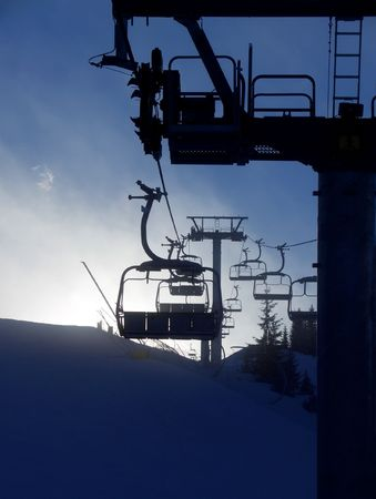 Chair lift silhouette on mountaintop, Friuli, Italy. Vertical. photo