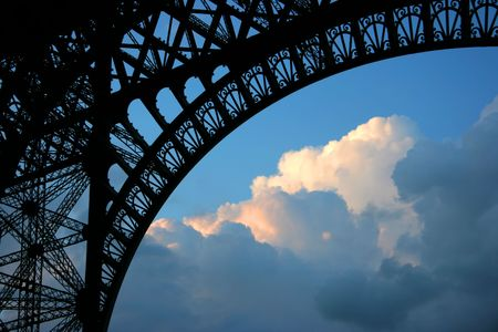 stormy clouds: Under Eiffel tower looking at stormy clouds hit by a warm sunset light