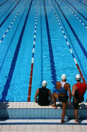 Drei Männer auf der Suche eine leere Schwimmbad, bereit für den Wettbewerb