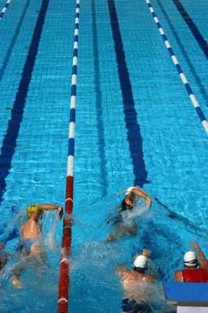swim race: Triathlon athletes entering the competition starting to swim Stock Photo