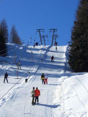 Menschen mit einem doppelten Skilift in Nassfeld, Österreich  Lizenzfreie Bilder