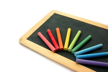 white chalks: Peque�a escuela de madera y pizarra en blanco de m�ltiples tizas de colores sobre fondo blanco aisladas