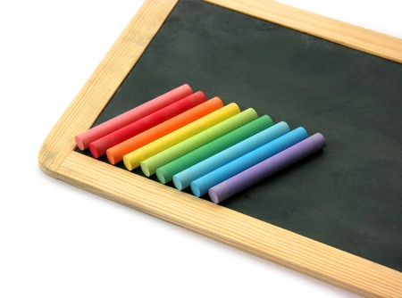 Small school wooden blank blackboard and multi color ordered chalks isolated on white background photo