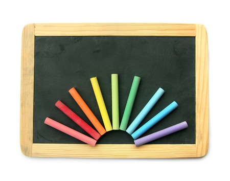 Small school wooden blank blackboard and multi color chalks isolated on white background photo