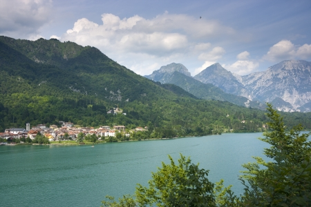 The green waters of Barcis lake, the mountains surrounding it and the village of Barcis itself in Valcellina, Pordenone, Italy Stock Photo - 14293780