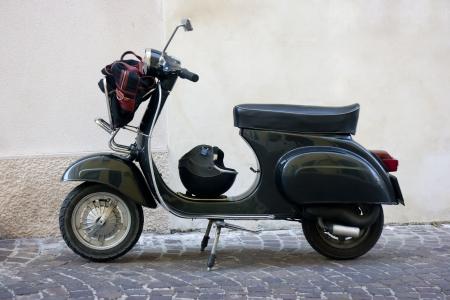 Seitenansicht von einem schwarzen Oldtimer Roller in einer kleinen Stadt in Italien Gasse Standard-Bild