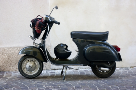 vespa: Vista lateral de un scooter negro vintage en un callejón pequeño pueblo en Italia