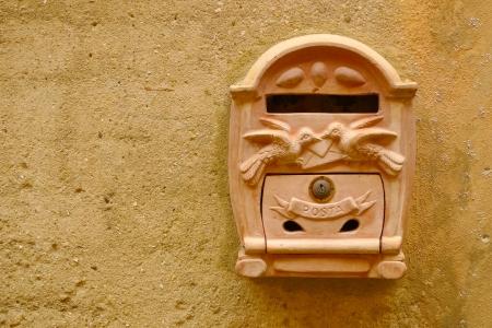 Terracotta-Mailbox auf eine gelbe Wand in Certaldo, Toskana, Italien.