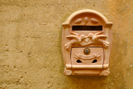 Terracotta mailbox on a yellow wall in Certaldo, Tuscany, Italy. photo