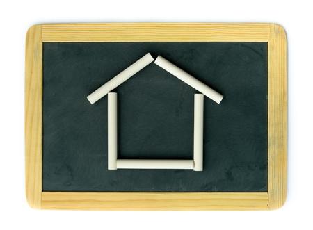 white chalks: Escuela peque�a pizarra en blanco de madera y tizas blancas que simulan una casa, aislados en fondo blanco Foto de archivo