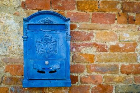 Blau Metall-Mailbox auf einer Mauer in Monteriggioni, Toskana, Italien.