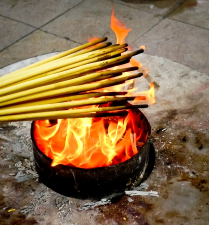 ignited: Incense sticks being ignited on a temple fire in Shanghai