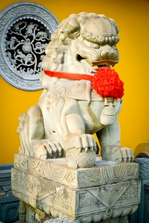 vigilant: Vigilant stone lion at the entrance of a Buddist temple in Shanghai, China Stock Photo