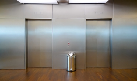 Two brushed metal elevator doors in a minimalistic style building interior photo