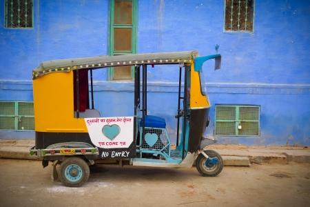 motorizado: Tradicional rickshaw motorizado againsta una pared azul en Jodhpur, Rajasthan, India