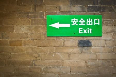 Green bilingual exit sign on grunge brick wall Stock Photo - 17753334