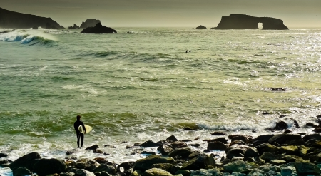 Surfer studying waves at Arched Rock beach, Sonoma County, California, USA photo