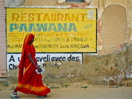 MANDAWA, RAJASTHAN, INDIA - August 9, 2009 - Woman in traditional dress walking in front of a restaurant street ad.