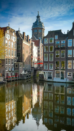 Amsterdam old town buildings and St Nicholas church dome reflecting on Oudezijds Voorburgwal Standard-Bild