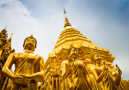 Niedrige Winkelsicht von goldenen stehenden Buddha-Statuen und von Haupt-chedi, Wat Phra That Doi Suthep, Chaing Mai, Thailand