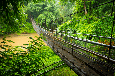 Suspension cable bridge across a river in the jungle near Chiang Mai, Thailand