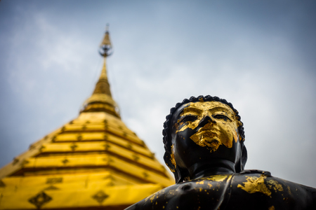 Low angle view of a black and gold Buddha and golden chedi, Wat Phra That Doi Suthep, Chaing Mai, Thailand Lizenzfreie Bilder