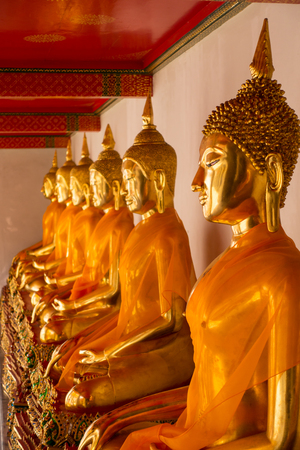 Row of sitting Buddha statues inside Wat Pho or Temple of the reclining Buddha, Bangkok, Thailand