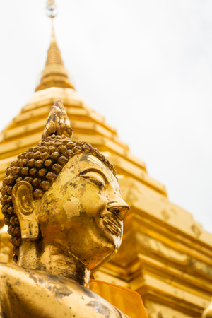 Low angle view of a golden Buddha and golden chedi, Wat Phra That Doi Suthep, Chiang Mai, Thailand