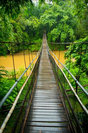 Zentrale vertikale Ansicht einer Suspendierungskabelbrücke über einem Fluss im Dschungel nahe Chiang Mai, Thailand