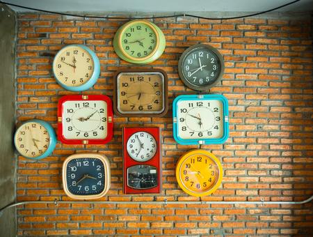 Einige Uhren auf einer Backsteinmauer, die verschiedene Zeiten zeigt.