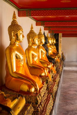 Reihe der sitzenden Buddha-Statuen, die nach rechts innerhalb Wat Pho oder des Tempels des stützenden Buddhas, Bangkok, Thailand gegenüberstellen