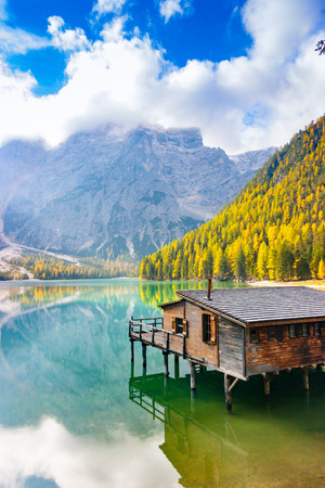 Vertical view of Prags lake, hut and Dolomites in autumn, Trentino Alto Adige, Italy Фото со стока