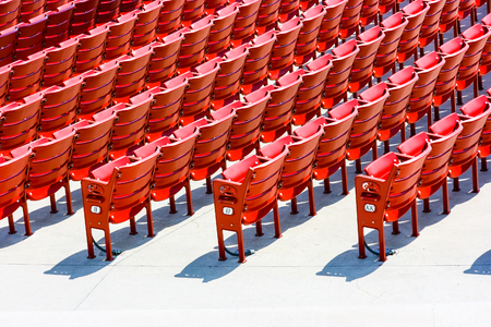Numbered rows of red plastic seats in an outdoor theatre, rear side landscape view