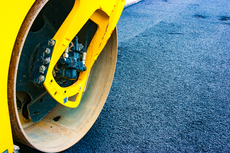 Detail of the front of a yellow roadroller on a newly laid asphalt. Stok Fotoğraf