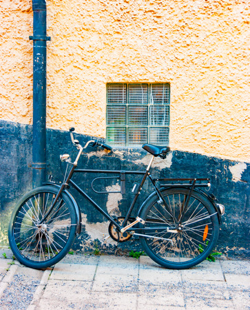 A black bike leaning against a black section of a wall with warm sunlight reflections in Stockholm, Sweden, Europe Imagens