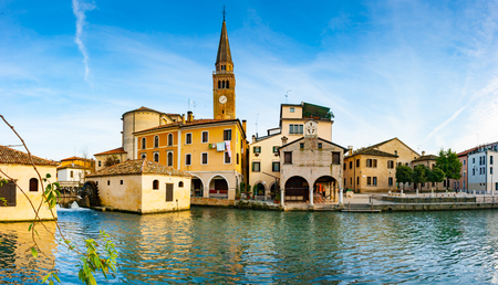 Panoramic view of Portogruaro with lemene river, St. Andrea clock tower and mills, Portogruaro, Veneto, Italy