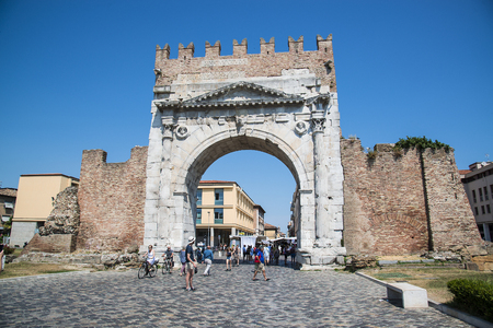 Rimini, Italy - June 21, 2017: Unidentified people walk under Augustus Arch - the ancient romanesque gate and the historical landmark of Rimini, Italy.