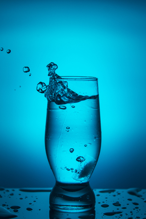 Splash of water in a glass on a blue background. Banque d'images - 106243897
