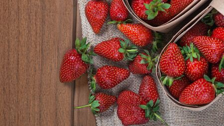 Fresh strawberries on a wooden table.