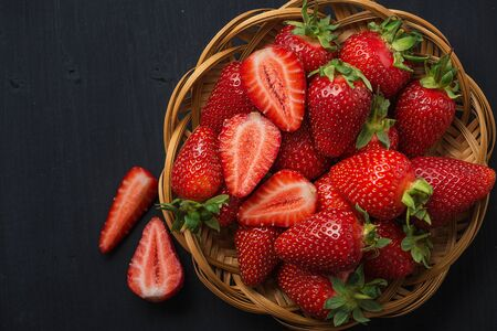 Fresh strawberries in a plate on a wooden table..