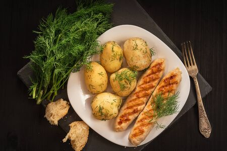Grilled chicken sausages with a side dish of potatoes and dill.