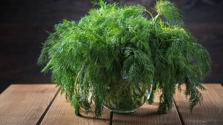 Fresh dill in a glass cup on a wooden table.