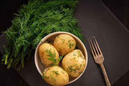 Boiled potatoes with dill in a plate on a black wooden table. 写真素材