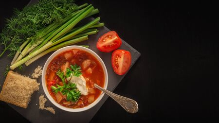 Borscht soup, bread and vegetables on a table of dark wood. 写真素材