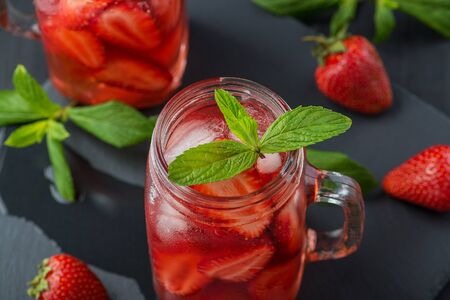 Fresh strawberry smoothie. Fresh summer cocktail with strawberries and ice cubes on a dark background on a black wooden table.