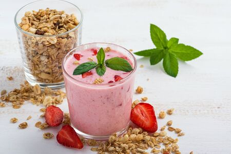 A glass of healthy strawberry yogurt with fresh berries, muesli and mint on a white wooden table. Healthy breakfast.