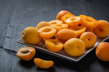 Fresh apricots on a black wooden table. 写真素材