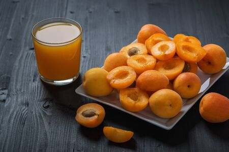 Fresh apricot juice and apricots on a wooden black table.