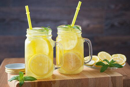 Lemonade in a jar with ice and mint on a black wooden table.